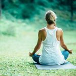 Young woman doing yoga, sitting in lotus