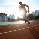 Afro american male runner practicing his sprint in athletics stadium racetrack